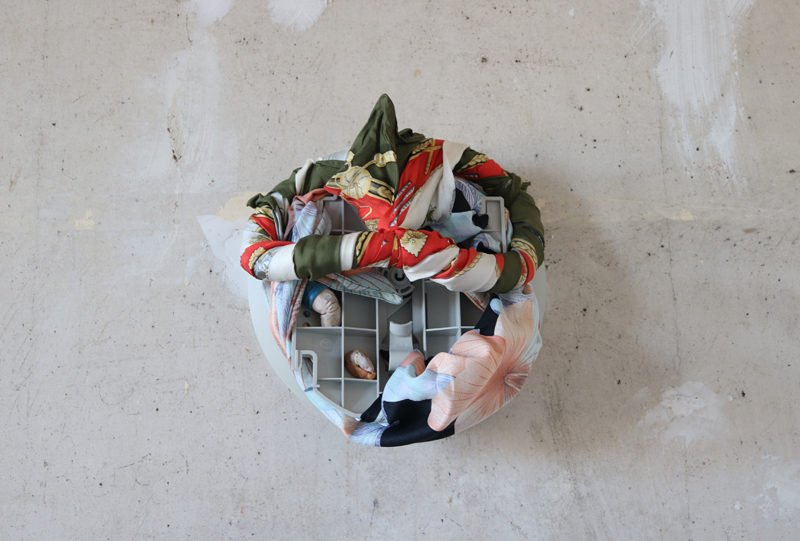 Upon a plastered wall is mounted a cluster of objects: a base from an old desktop computer monitor, two colouful head scarves boasting blooms of red, gold, green, blue, black and pink. Furthermore, fitted into the structure of the monitor base, are two clay objects.