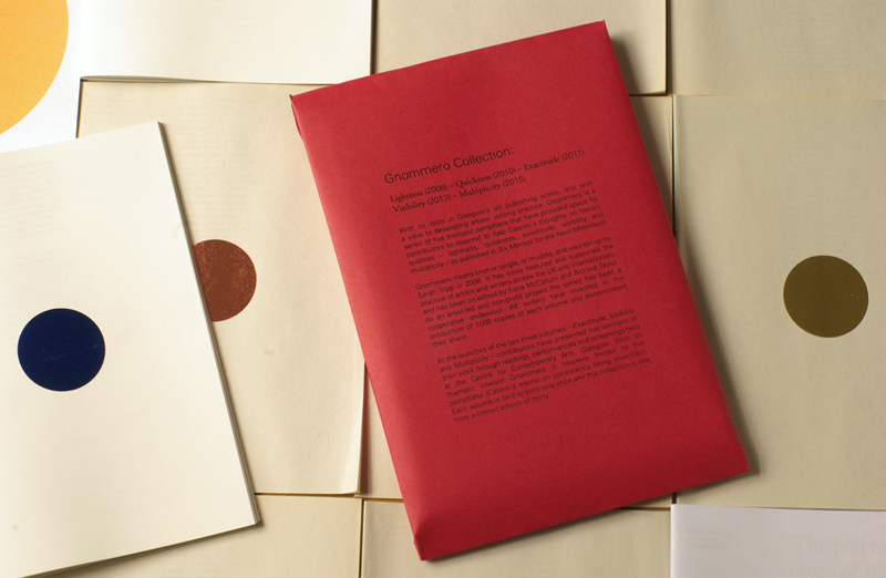 An image showing issue from the Gnommero series. White and brown paper publications with coloured dots in the middle. In the centre lies a bright red envelope with text, with the title 'Gnommero Collection'. Copy-editing for the contents of these photographed publications was conducted by myself and Sarah Tripp, in Glasgow.