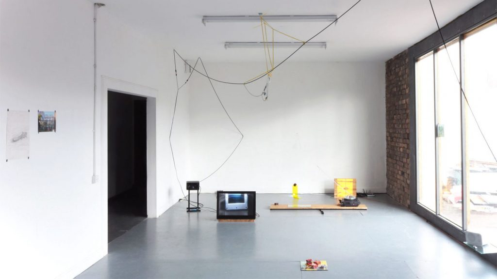 A room with a tall ceiling and white walls, a entrance from the left and a floor to ceiling window on the right, with brick surround. Within the room is an installation of objects, cables, wood, a gaming monitor, a slide projector and speakers. There is a small sculpture on the floor in the foreground, and to the left, in the foreground and on the wall, is a drawing and a photograph.