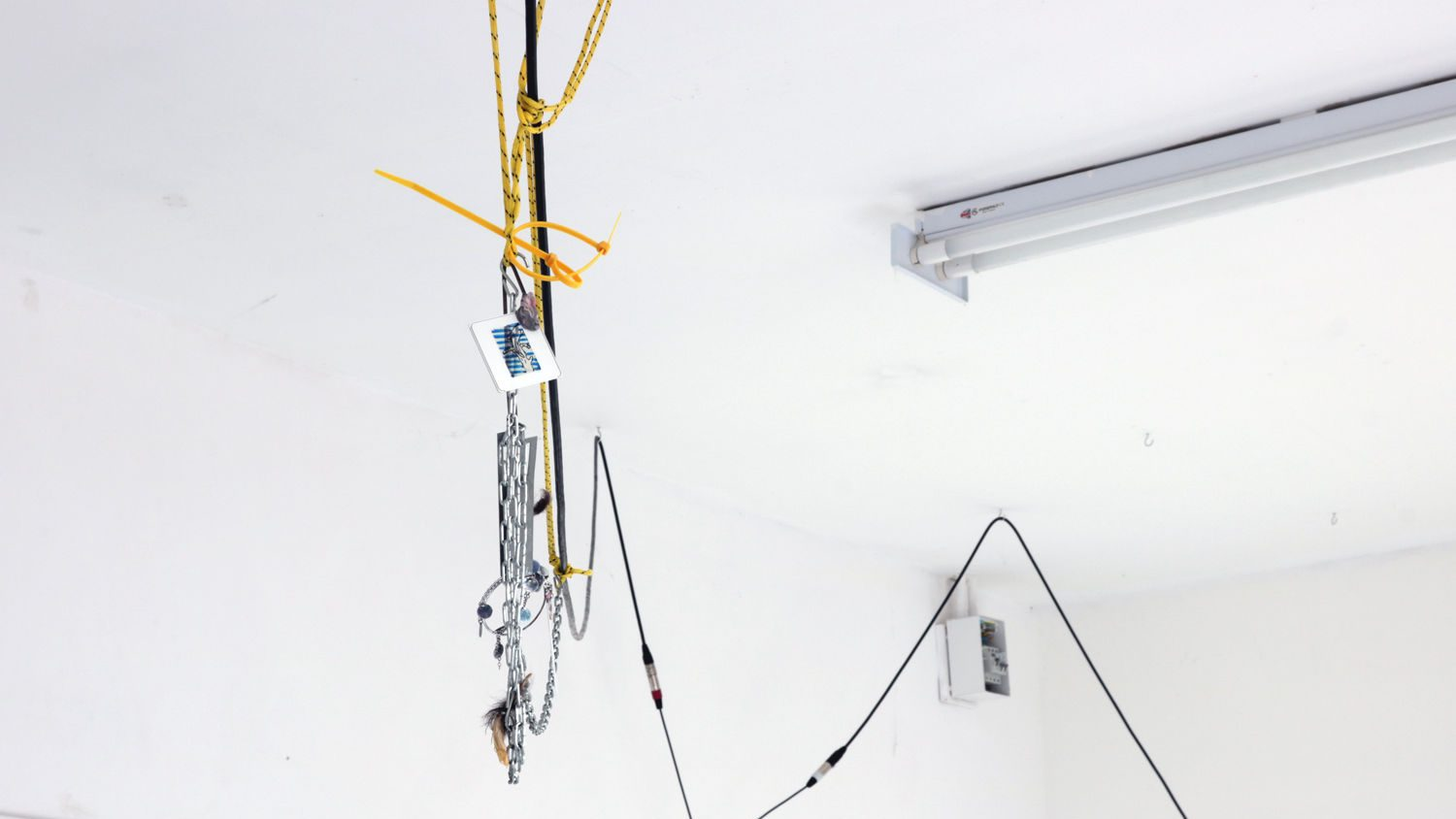A sequence of objects, yellow and black rope, and XLR cables entwined and hanging from the ceiling in a white room. The objects include 35mm slides in mounts with drawings on them, earrings, cactus flowers and yellow cable ties.