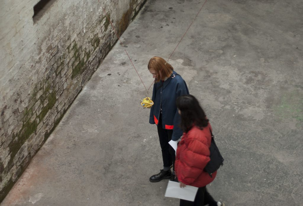 Two people wearing coats in an industrial setting, who are focussing their eyes on a small yellow sculpture suspended from the roof. The encounter is very intimate.