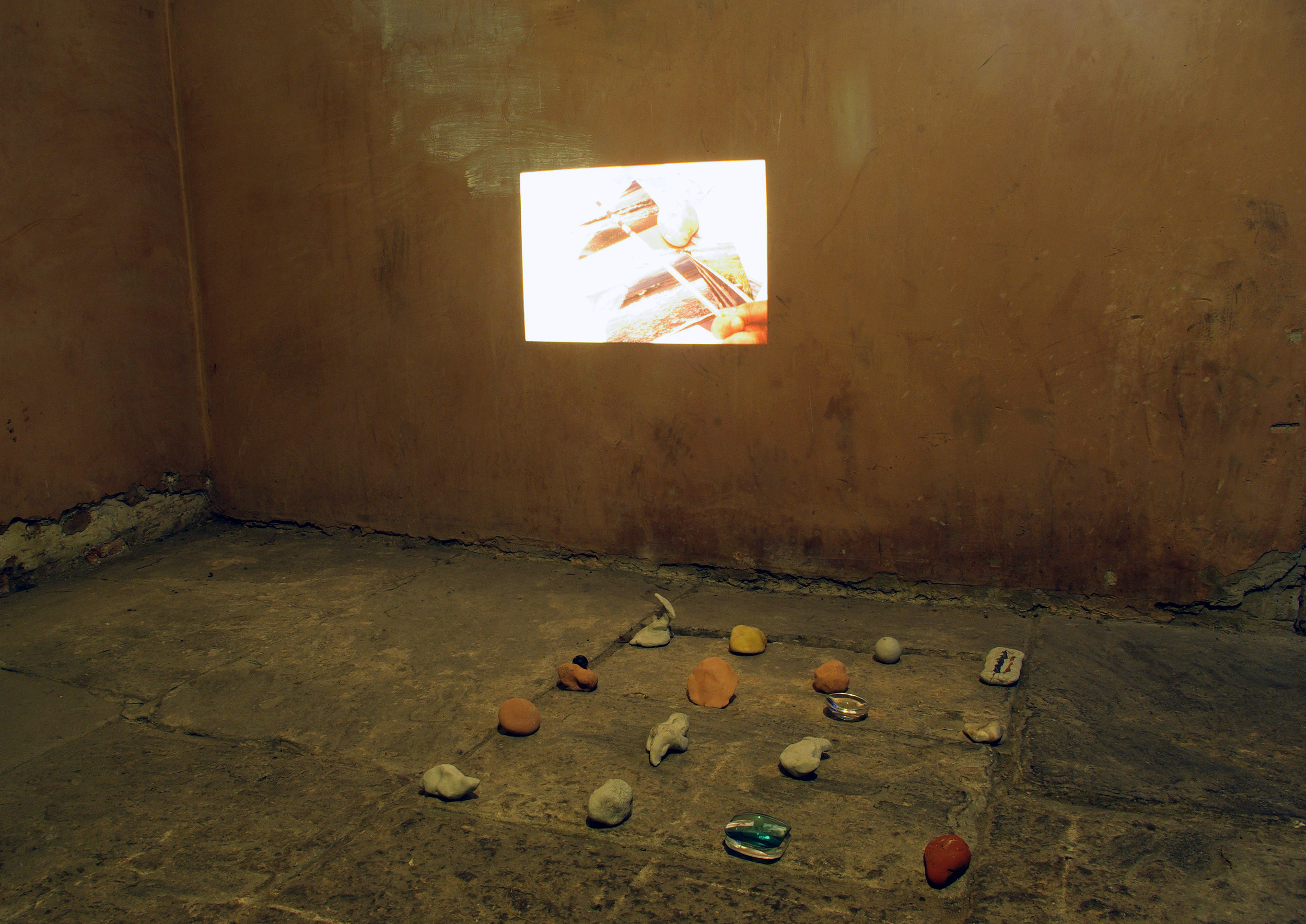 Richard Taylor artist and editor exhibiting at Basement Arts Project in Leeds, UK, 2013. Turnip prize winner and expert slide photography projection with stones and unfired clay objects.