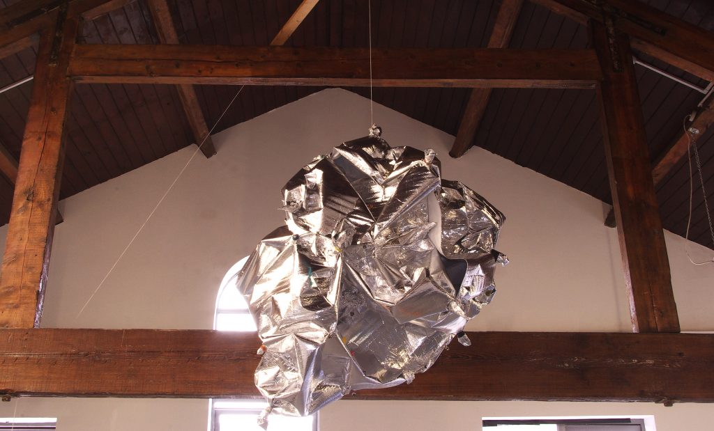 Enjoy sculpture and installation by Richard Taylor artist and editor. A hanging silver object in an old building in Leeds, UK.