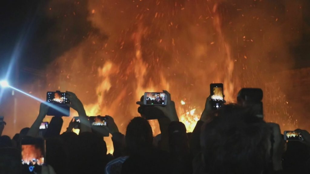 Click this image to load a lightbox window to view the video entitled 'Field Pub'. The content of this image has a bonfire out of focus in the background, with a silhouetted crowd in the foreground. The crowd are holding up mobile phones to take pictures of the bonfire. Richard Taylor artist and editor: Sound and Video production.
